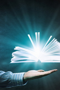 a bright glowing book floating above an open hand