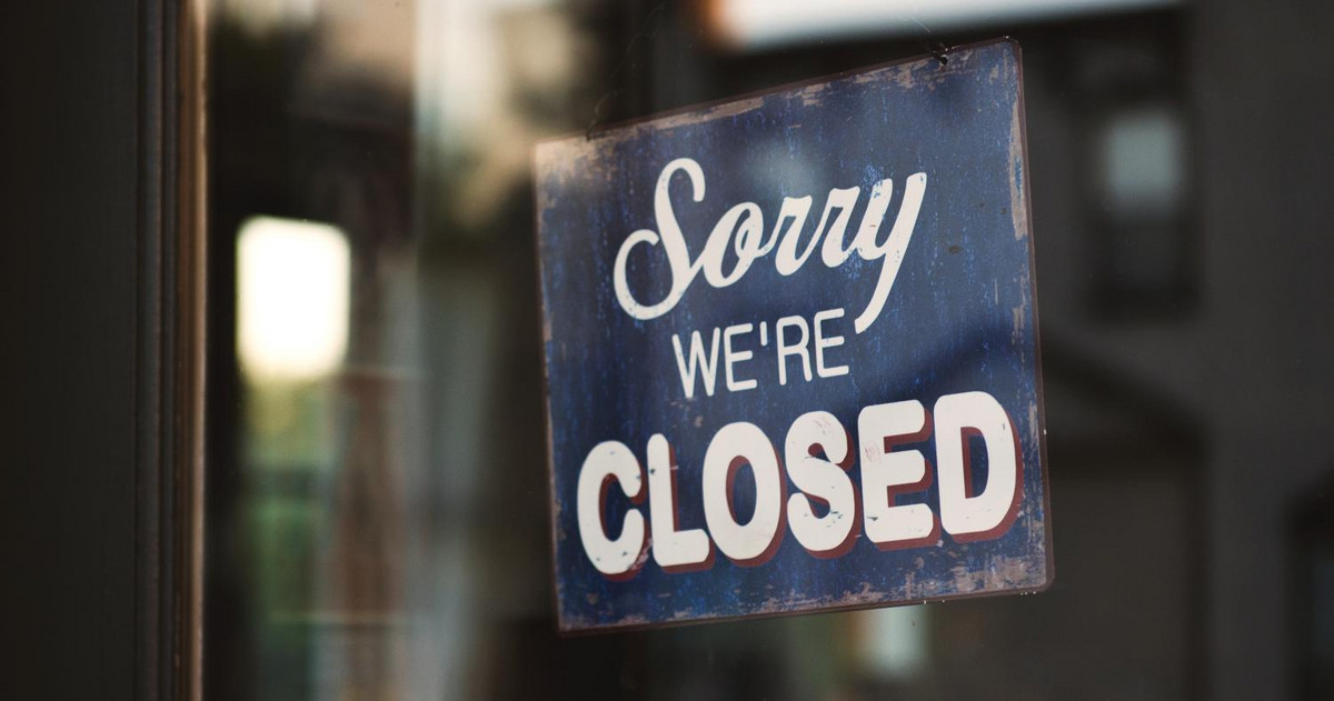 Pic of a closed sign within a shop window
