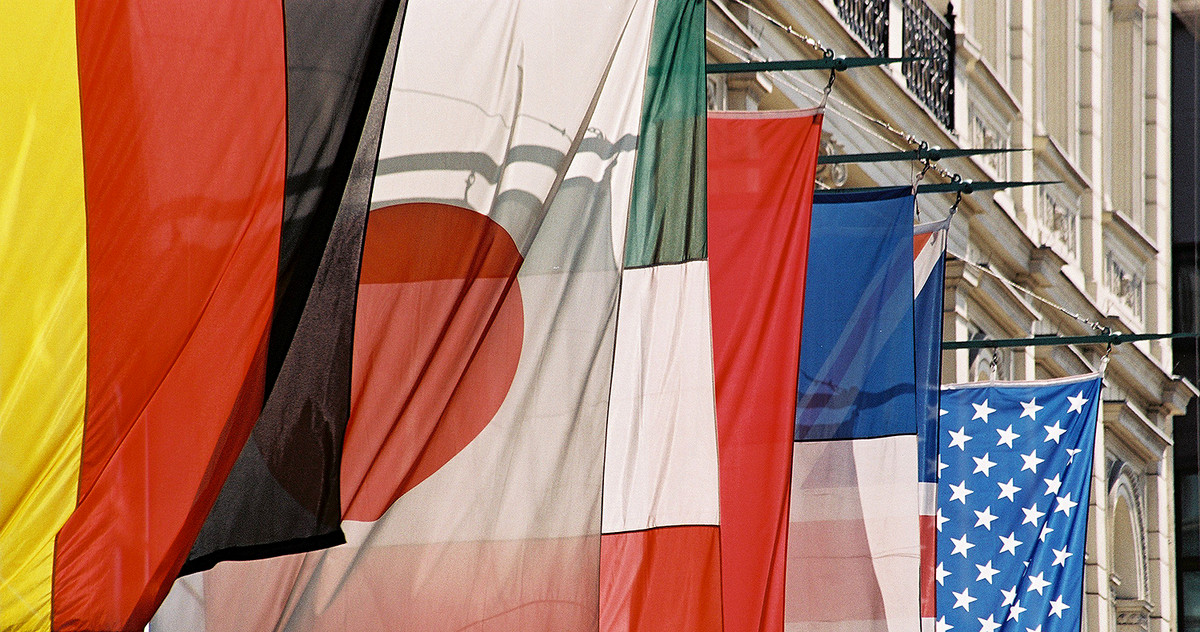 Picture of numerous flags hanging on a building