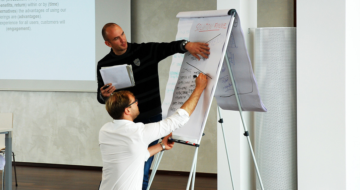 Two men working out ideas on a flipchart