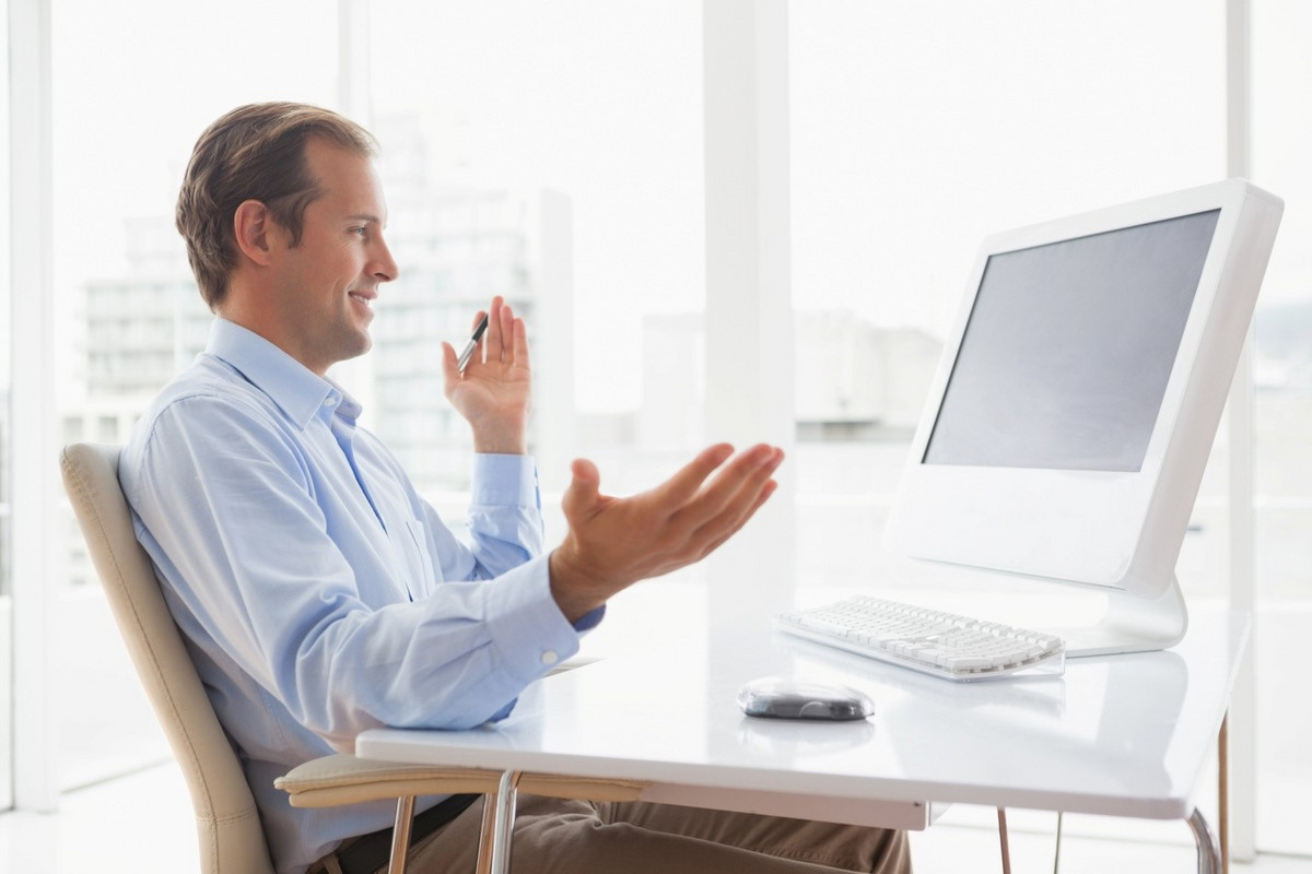A young business man gesturing in front of his computer