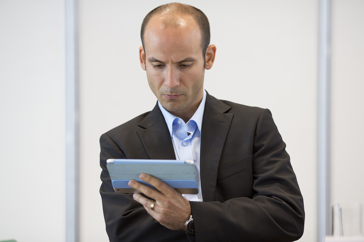 A business man looking concentrated at his tablet computer