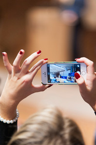 Woman holds iPhone in her hand and films an event