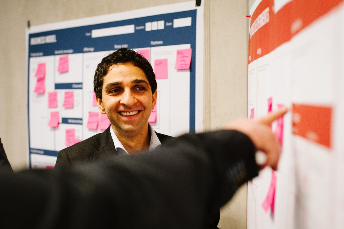 A young business man looking at a white board while someone is pointing at notes on the white board