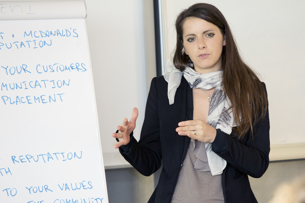 Young business woman presenting in front of a flip chart