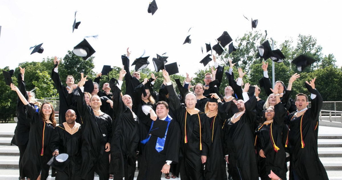 Picture of students throwing a graduation hat