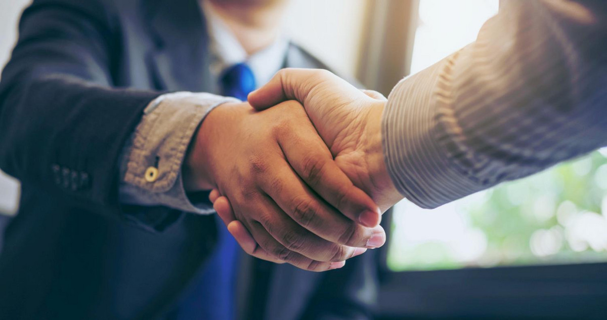 two man shaking hand over a loan for a global MBA program