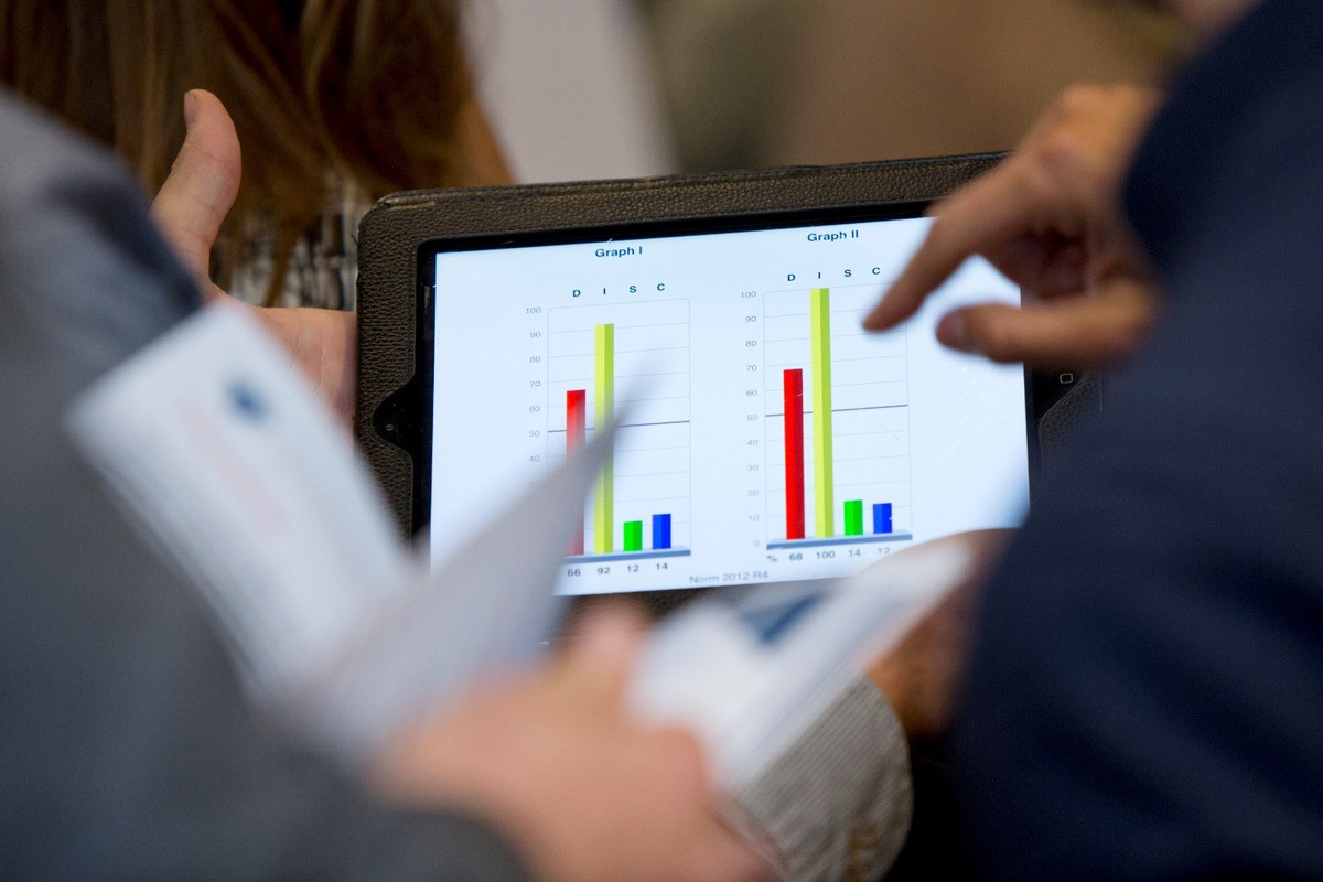 Two people pointing at a tablet showing data charts