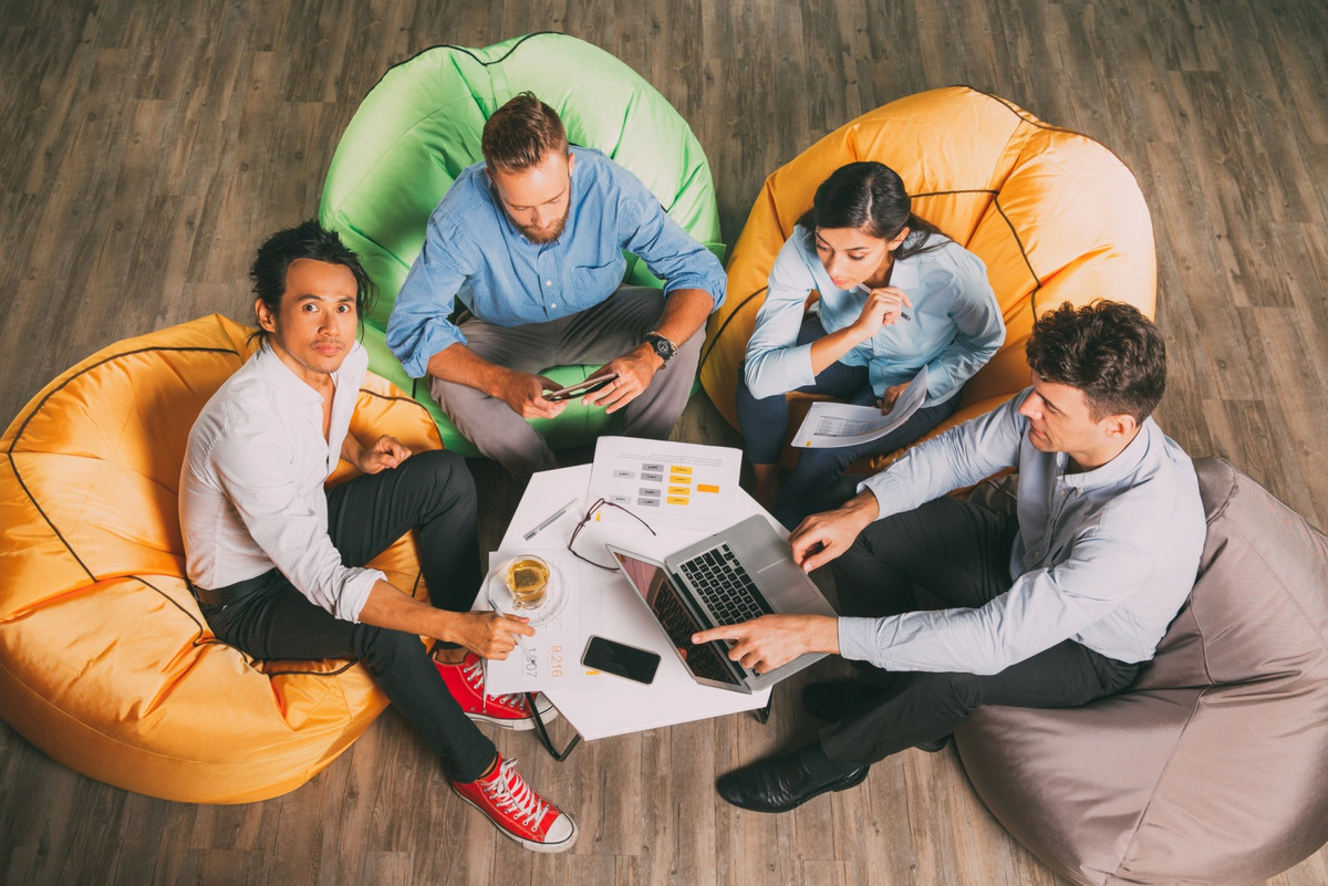 4 young people sitting on huge bags on the floor, working together on a laptop