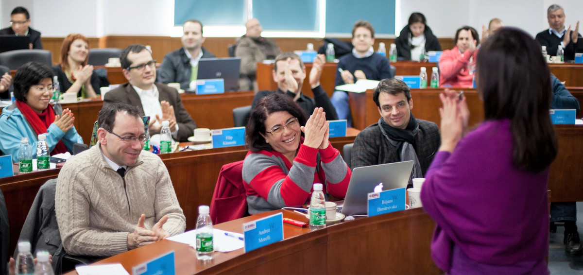 Many students sit in front of a professor and are smiling
