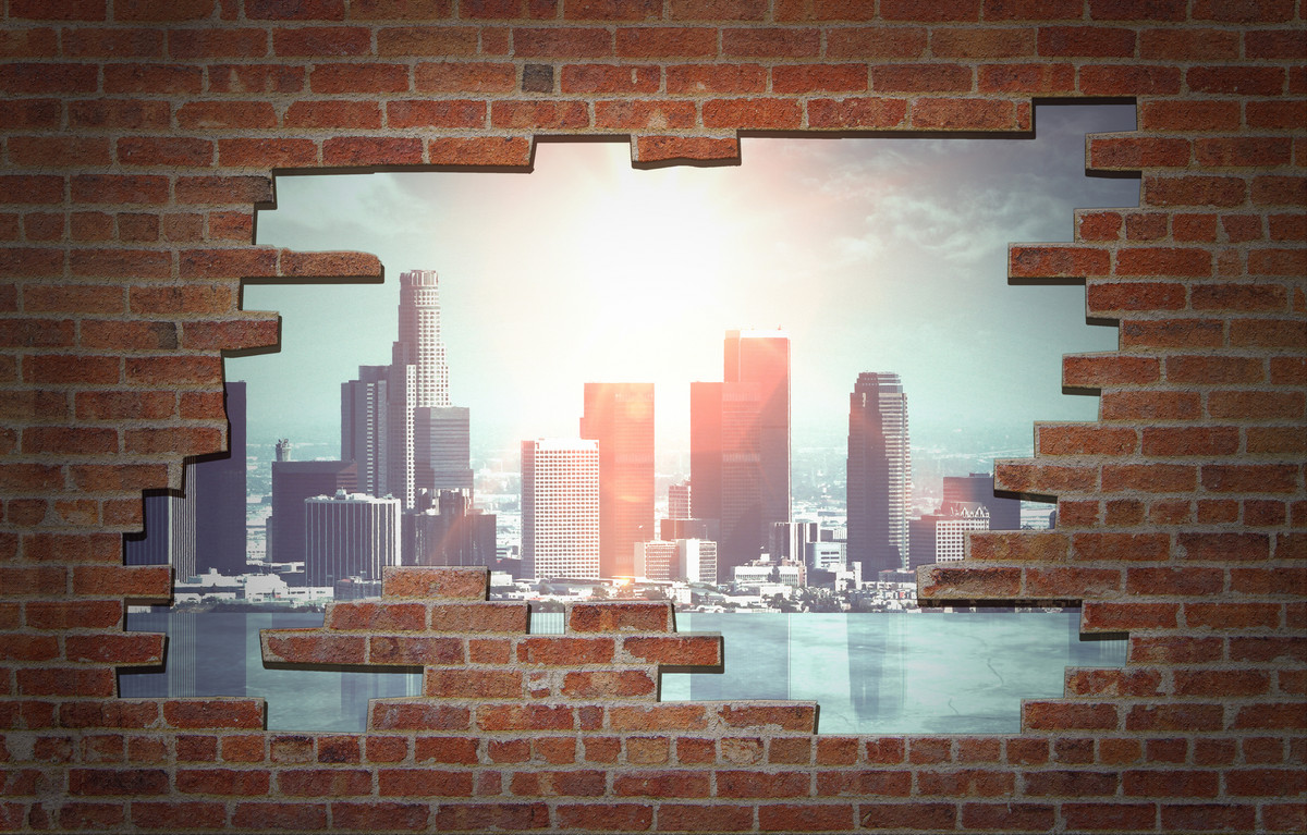 Broken red brick wall with city view