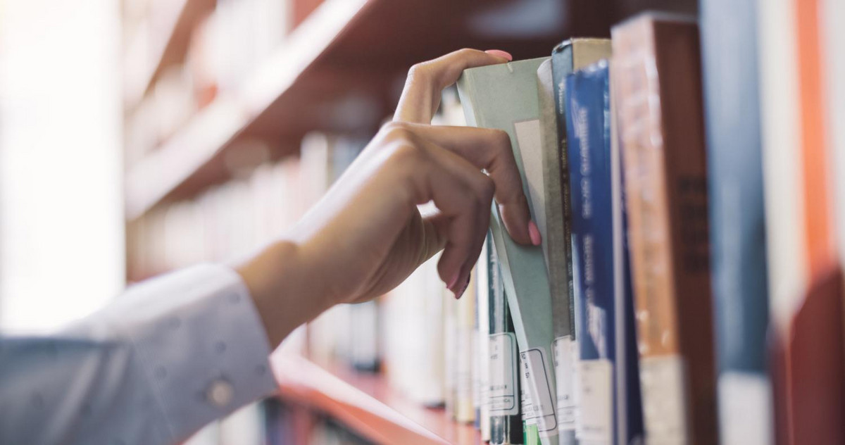 An MBA student is taking a book out of a shelf