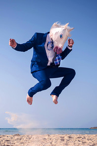 A man in a suit wearing a unicorn mask is jumping on the beach