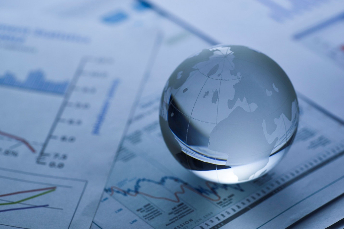 A glass globe of the world resting on some business sheets