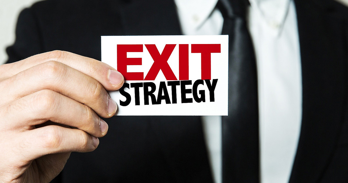 "Man holding a sign that says: ""Exit Strategy"""