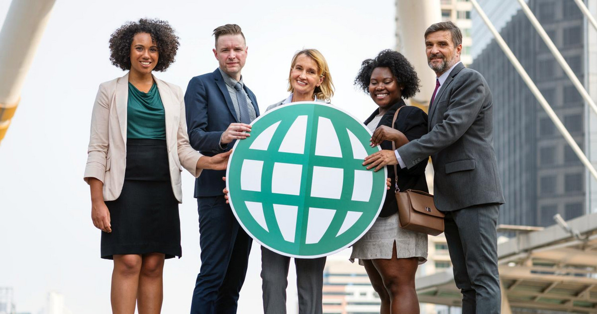 MBA students holding a globe together
