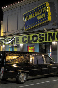 a hearse parking in front of a closed Blockbuster Videos store