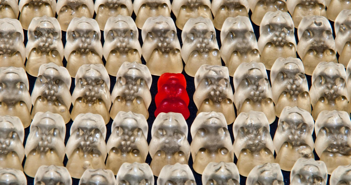 Picture of a red jelly bear, standing out of a white crowd