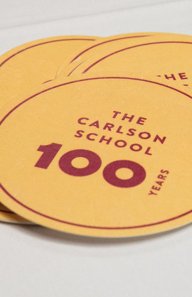 "A golden coin with ""100 years Carlson University"" written on it in red"