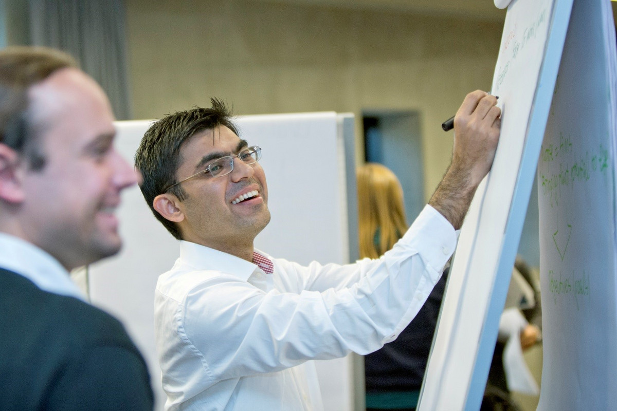 Two smiling business men drawing on a flip chart