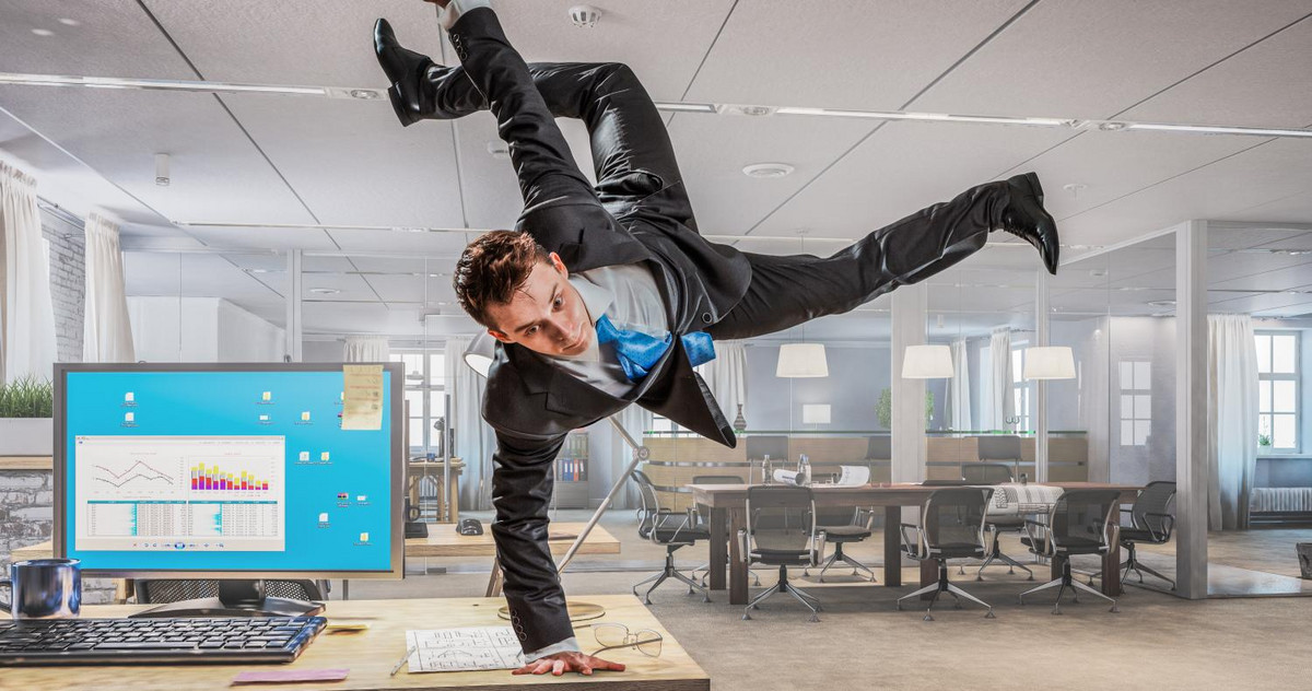A man is breakdancing in the office