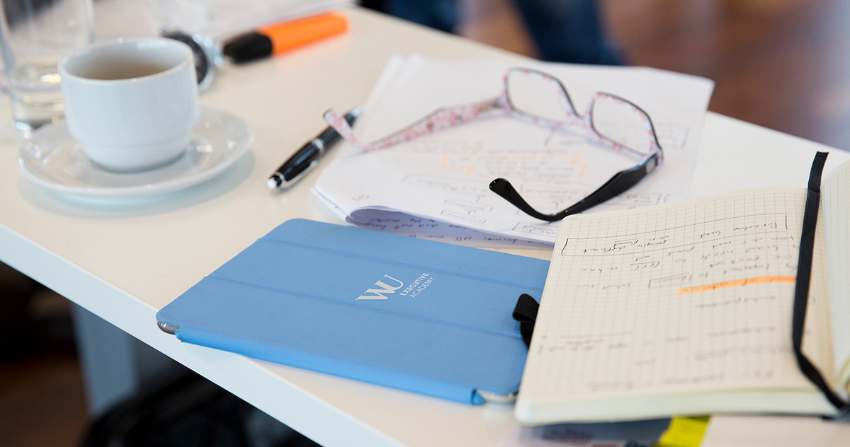 Picture of a table with a notebook, glasses and a tablet on it