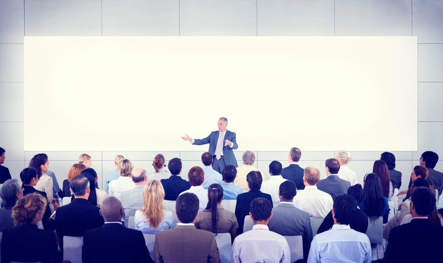 A man presenting in front of a big audience
