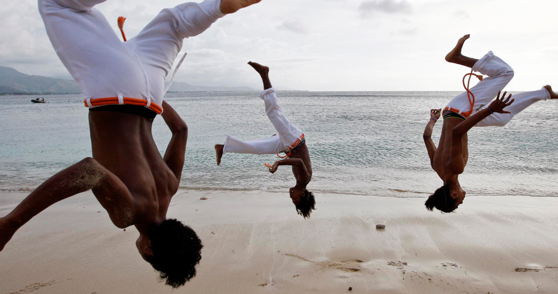 Three men doing Capoeira on a beach, the ocean in the backgroung